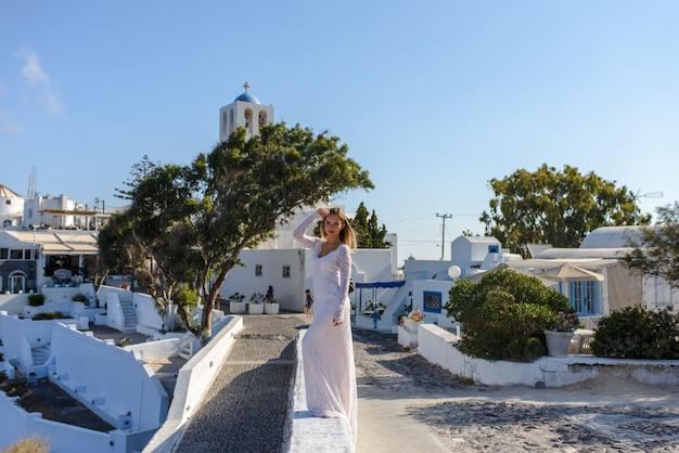 Noiva linda em um vestido branco posando contra o pano de fundo da cidade de thira, santorini.