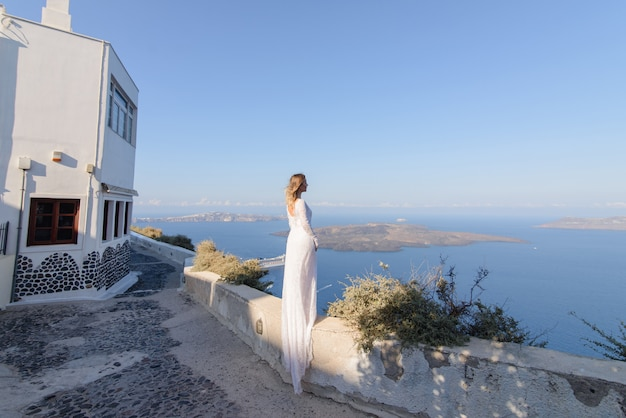 Noiva linda em um vestido branco, posando no contexto do mar mediterrâneo em thira, santorini.