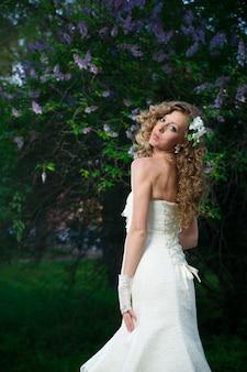 Noiva linda em um vestido branco sobre fundo lilás na primavera