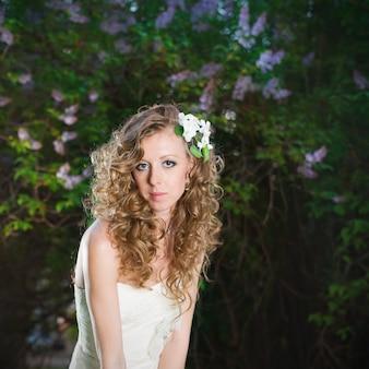 Noiva linda em um vestido branco sobre um fundo lilás na primavera. maquiagem e penteado profissionais