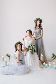 Noiva linda em um vestido de noiva branco segurando o buquê e sentado na cadeira vintage com damas de honra em vestidos cinza azuis e grinaldas