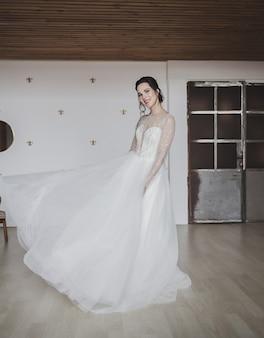 Noiva linda em um vestido de noiva luxuoso dentro de casa