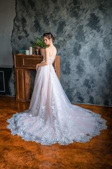 Noiva linda em um vestido longo pela janela