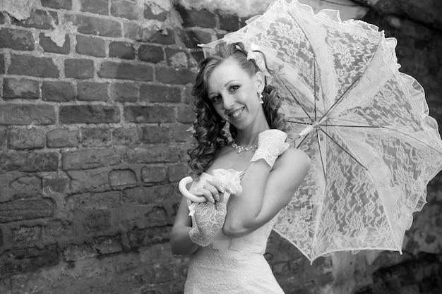 Noiva linda em vestido branco com guarda-chuva