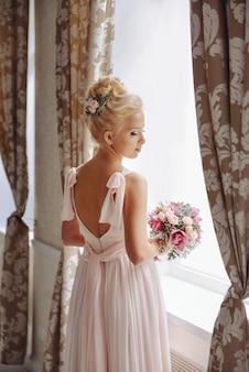 Noiva linda jovem com buquê de rosas e orquídeas em pé perto da janela
