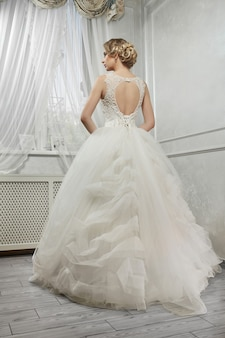 Noiva linda jovem, mulher de vestido de noiva branco longo na whit