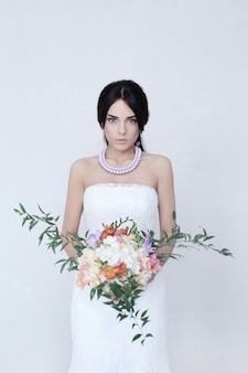 Noiva linda mulher vestida de noiva, segurando um buquê de flores