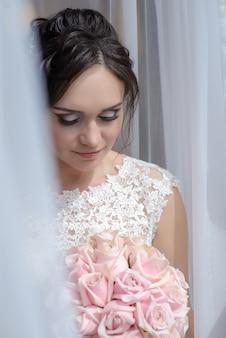 Noiva linda na janela, olhando para um buquê de rosas