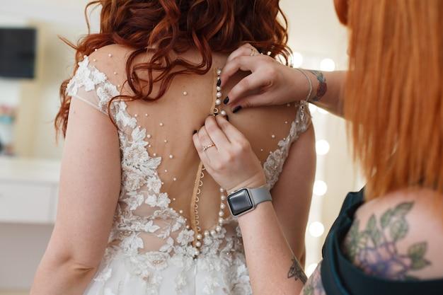 Noiva linda no vestido com as costas nuas interior. a noiva usa um vestido na manhã do casamento de perto. garota atraente magro veste vestido apertado. mão feminina, abotoando o vestido de casamento branco. dia do casamento