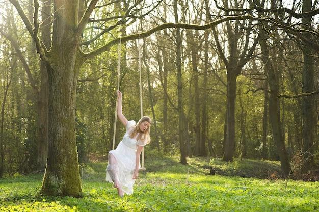 Noiva linda no vestido de casamento branco sentado no balanço ao ar livre