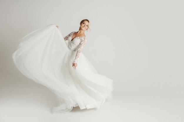 Noiva linda no vestido de casamento com saia longa cheia em branco