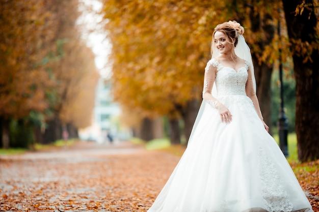 Noiva linda no vestido de casamento de moda em plano de fundo natural. a noiva jovem deslumbrante é incrivelmente feliz. dia do casamento