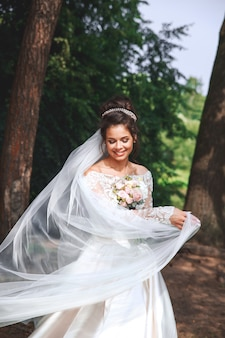 Noiva linda no vestido de casamento em natural ao ar livre. dia do casamento.