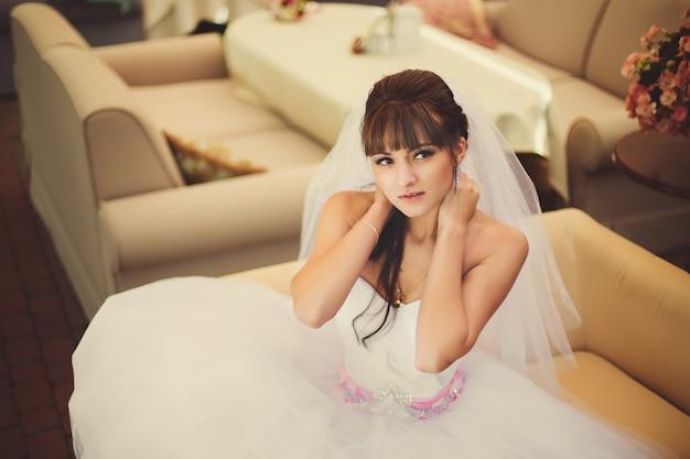 Noiva linda no vestido de casamento no interior de luxo com jóias com diamantes, posando em casa e esperando o noivo. romântica rica garota feliz em vestido de noiva