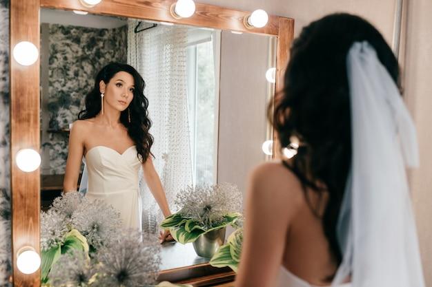 Noiva linda no vestido de casamento, olhando no espelho