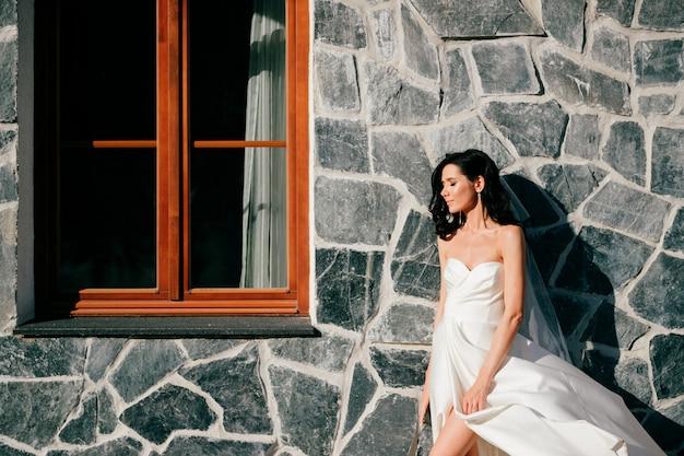 Noiva linda no vestido de casamento, posando sobre parede texturizada com janela.