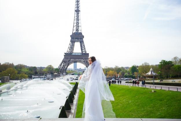 Noiva linda num vestido de noiva rico gira na praça antes da torre eiffel