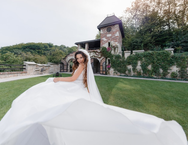 Noiva linda sorriu em vestido de luxo no quintal da grama do edifício antigo,