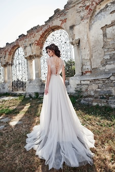 Noiva linda, vestido de noiva, que é fotografado no dia do casamento, perto do castelo velho.