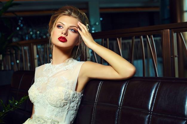 Noiva loira elegante de glamour com maquiagem brilhante e lábios vermelhos