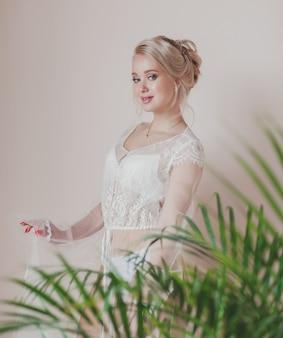Noiva loira linda em um vestido de casamento na sala. manhã da noiva e preparação para o casamento