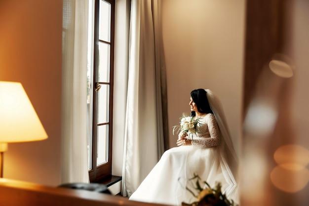 Noiva loira linda no vestido de casamento de luxo e damas de honra lindas gêmeas em vestidos semelhantes em uma manhã em um espaço loft com um espelho e uma guirlanda de lâmpadas.