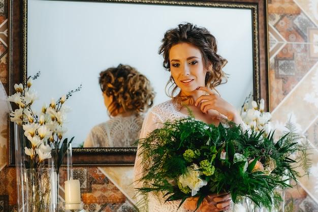 Noiva luxuosa em um lindo manto de renda com um buquê de flores e folhagens