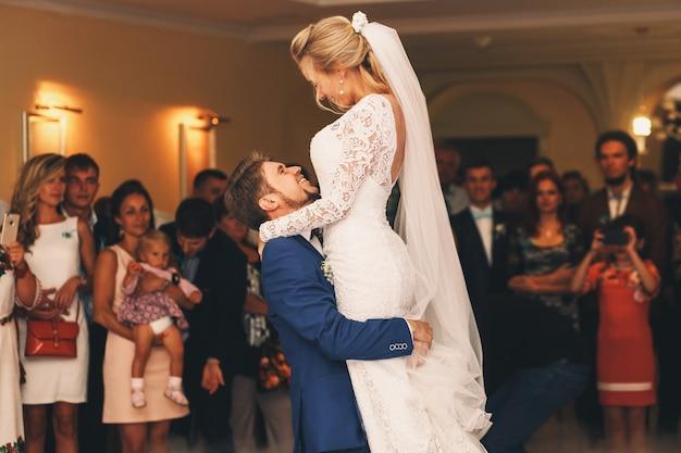 Noiva mantém as costas retas enquanto o noivo a levanta durante a dança