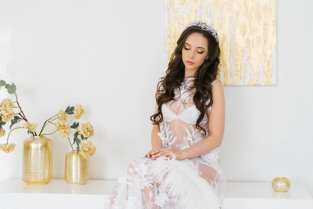 Noiva morena bonita linda no vestido boudoir com tiara no penteado.
