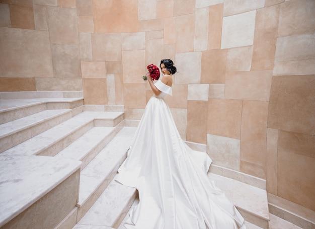 Noiva morena caucasiana de luxo está de pé nas escadas perto da parede de pedra e segurando o buquê de casamento de peônias vermelhas
