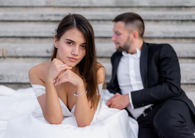 Noiva morena com seios grandes está olhando em linha reta e um noivo está sentado no fundo