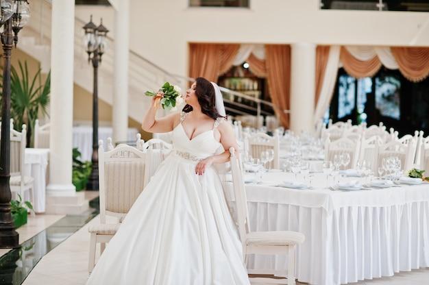 Noiva morena de seios grandes com buquê de casamento colocado em mesas de fundo de salão de casamento