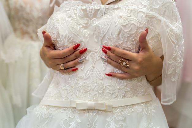Noiva morena experimenta vestido de noiva no salão