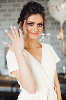 Noiva morena mostrando a mão com aliança e rosto escondido.