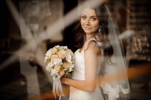 Noiva morena sorrindo e segurando o buquê de rosas