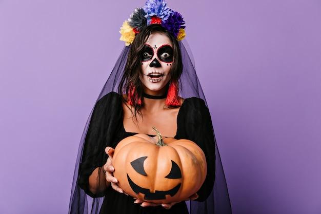 Noiva morta com abóbora nas mãos, expressando espanto. senhora chocada com fantasia de halloween com a boca aberta.