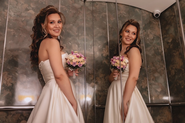Noiva muito jovem no elevador com espelho grande. manhã da noiva no dia do casamento. noiva feliz com buquê nas mãos desce no elevador para encontrar o noivo. espaço de direitos autorais