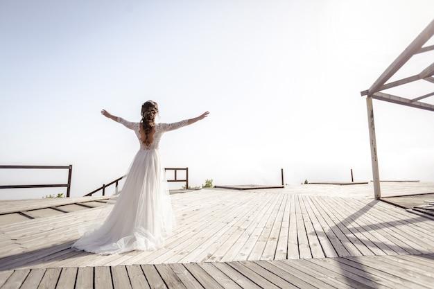 Noiva mulher em um vestido branco outdors