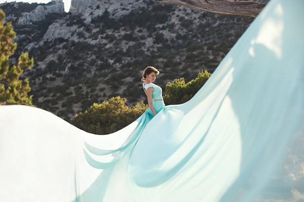 Noiva na natureza nas montanhas perto da água. cor do vestido tiffany. a noiva está brincando com o vestido dele.