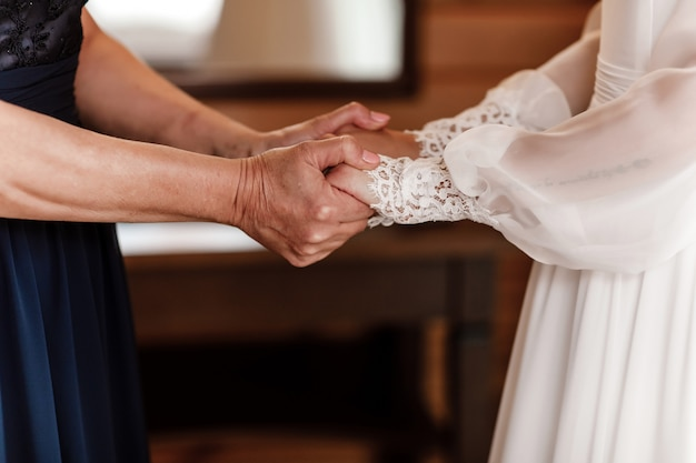 Noiva no dia do casamento segurando as mãos da mãe