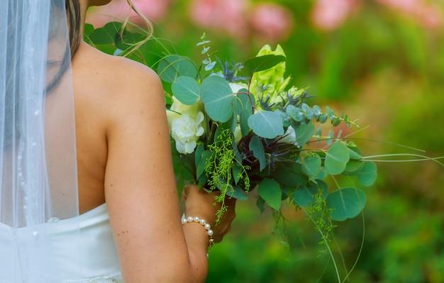 Noiva no jardim detém buquê retrô