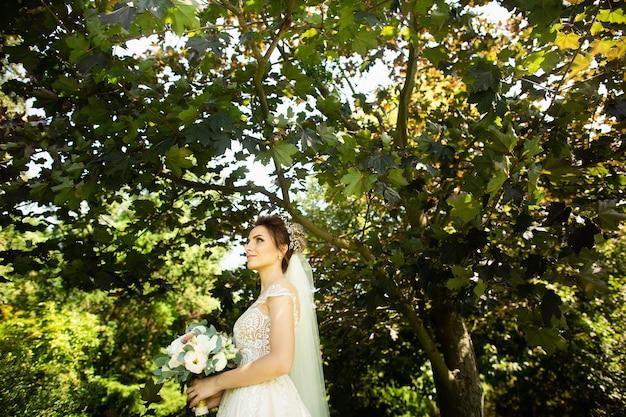 Noiva no vestido de casamento da fôrma no fundo natural. um, mulher bonita, retrato, parque