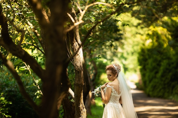 Noiva no vestido de casamento da fôrma no fundo natural. um retrato bonito da mulher no parque. vista traseira