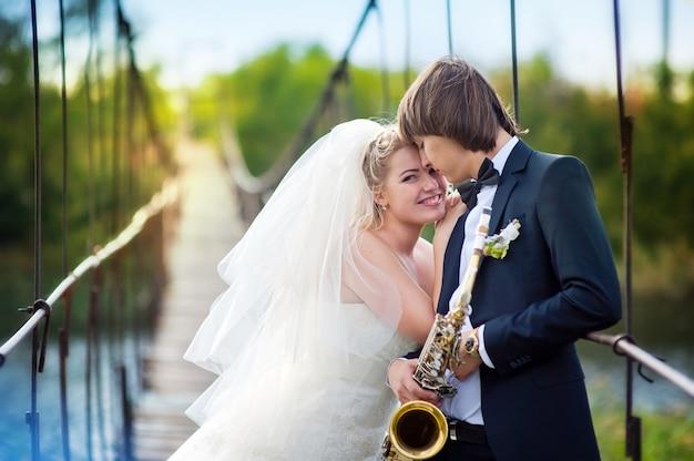 Noiva noivo, com, saxofone, ficar, ligado, ponte