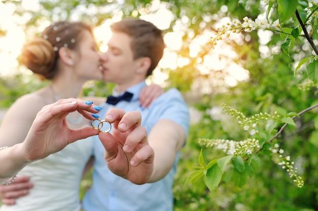 Noiva noivo, segurando, anéis, e, beijo