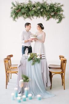 Noiva noivo, segurando, bolo casamento, desfrutando, refeição, em, recepção casamento, decorado, com, pinho, e, velas