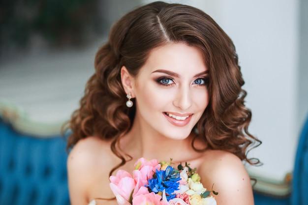 Noiva nova bonita com maquiagem e penteado de casamento interior. closeup retrato da jovem noiva linda