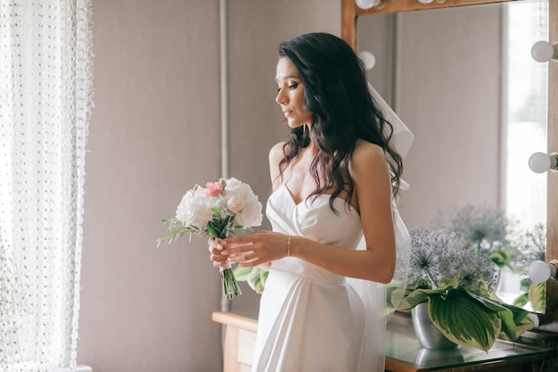 Noiva nova bonita no retrato interno do vestido de casamento branco