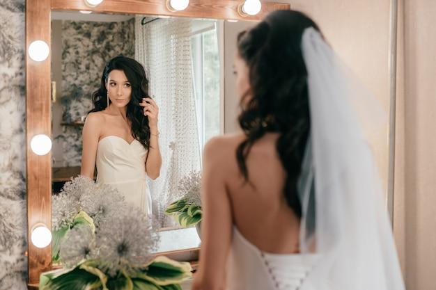 Noiva nova bonita no vestido de casamento branco que olha no espelho.