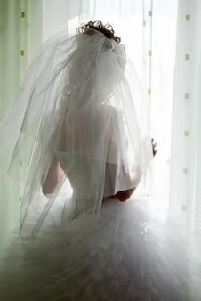 Noiva parece fora da janela, dia do casamento